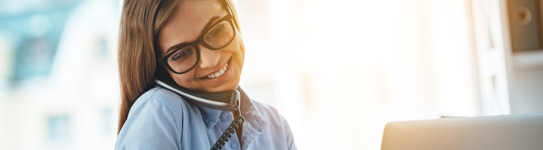 Woman with glasses on her landline phone from Alpine Communications