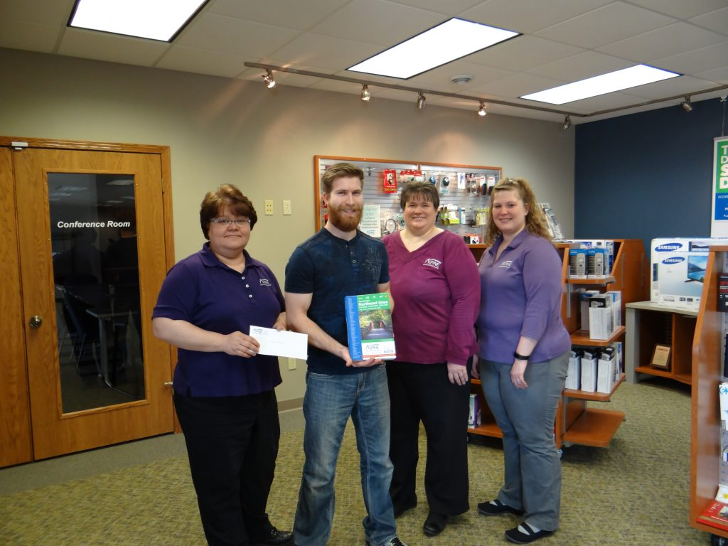 Presenting a $50 gift certificate to Dustin Kilburg is Lori Keppler, Margaret Corlett, and Melissa Schilling from Alpine Communications